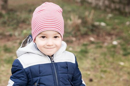 portrait of a three year old boy looking at camera dressed in warm clothes against the background of the autumn park. Outdoor. Childhood concept.