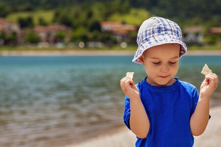 Cute baby boy 3 year old who eating snack with satisfaction against the background of the lake. Outdoor. Childhood concept. Zdjęcie Seryjne