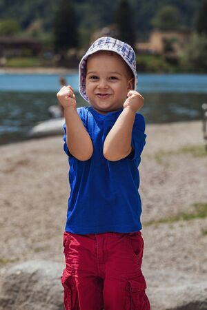 Cute baby boy 3 year old expressing happiness and satisfaction with his face and hands against the background of the lake. Outdoor. Childhood concept.