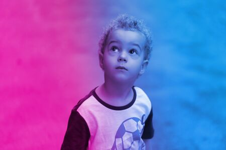 Cute baby boy 3 year old looking thoughtfully upwards in the theme of blue and magenta neon. Outdoor. Childhood concept. Zdjęcie Seryjne