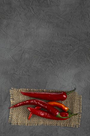 Ugly chili hot peppers on dark slate, lay flat from above. Cooking concept
