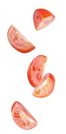 Flying in air fresh slice tomatoes isolated on white background with clipping path as package design element and advertising. Full depth of field, flat lay. Professional studio photo.