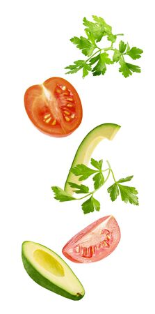 Flying vegetables. Falling avocado, parsley and tomatoes isolated on white background with clipping path as package design element and advertising. full depth of field