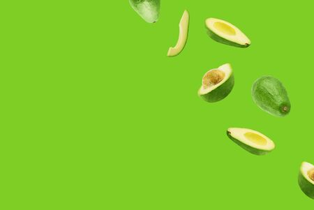 Frame made of fresh whole and sliced avocado on trendy green background. Flat lay, top view, copy space