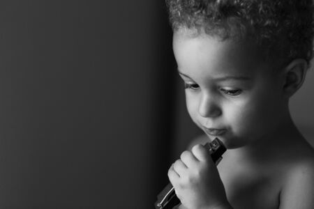 Cute baby boy 3 year old playing the harmonica, Indoor. Childhood concepton. Black and White.