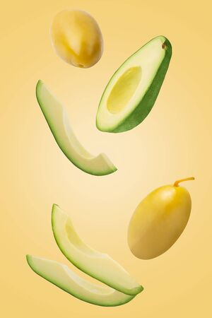 Falling green pickled olives and avocado isolated on yellow background. Zdjęcie Seryjne - 140234444