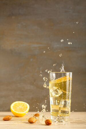 Homemade lemon kombucha fresh ice tea in a trasparent glass on a gray background drink close up. vertical view with copy space for text. Selective focus.