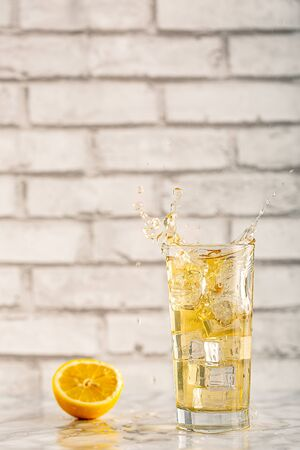Splashing homemade lemon kombucha fresh ice tea in a trasparent glass on a gray background drink close up. vertical view with copy space for text. Selective focus. Zdjęcie Seryjne - 141915295