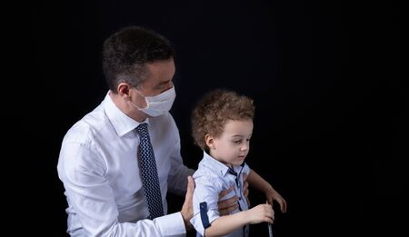 Businessman with medical mask working from home. Little son who wants to be in his arms. Black background. Banner with copy space for text. Zdjęcie Seryjne