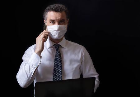 Businessman with medical mask working from home on laptop and talking on the phone. Black background. Banner with copy space for text. Zdjęcie Seryjne