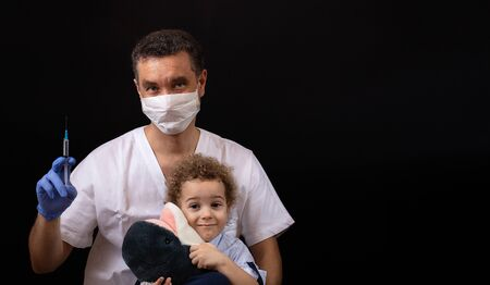Beautiful medical worker, pediatrician, with medical mask and gloves working. Protection during Coronavirus epidemy. Pandemia of Covid-19, quarantine. selective focus. Black background with copy space