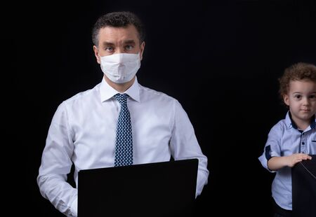 Businessman with medical mask working from home on laptop and the son who looks at him from behind. Black background. Banner with copy space for text.