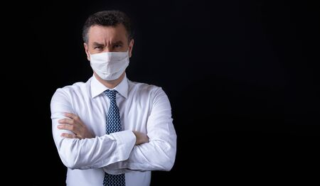 Closeup portrait angry businessman wearing a surgical mask with crossed arms on black backround. Pandemic effect of coronavirus. Copyspace for your text.