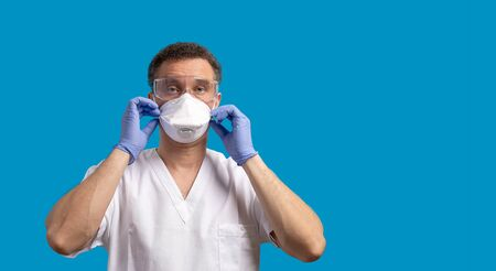 N95 Face Mask. Surgeon prepares to enter the operating room during the coronavirus period, wearing personal protective equipment. Medical gloves, mask and glasses. Blue backgraund. Banner with copyspace for text. Zdjęcie Seryjne