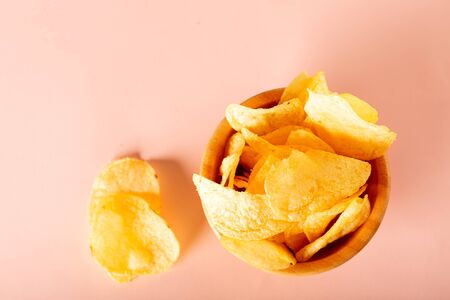 Top view snacks with crispy potato chips in bowl on a pastel colored table. fast food concept. Flatlay with copy space,