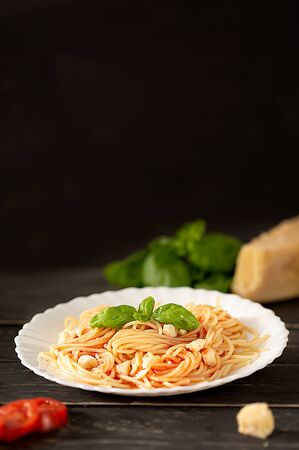 Italian cousine. Fresh spaghetti pasta with tomato sauce, seasoned parmesan and fresh leaves of basil on dark table. Healthy vegetarian food. Copy space and soft focus.
