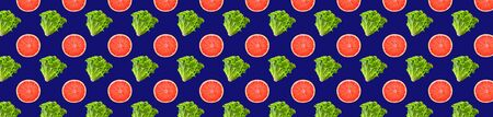Creative seamless pattern food. Fresh mix of green gentile lettuce salad and grapefruit slices on classic blue background. Full depth of field. Horizontal banner.