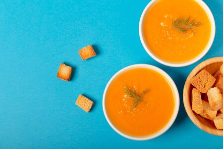 Minimal healthy food. Bowls with pumpkin and carrot cream accompanied with croutons. Vegan food. Top view. Horizontal wit copyspace. Zdjęcie Seryjne
