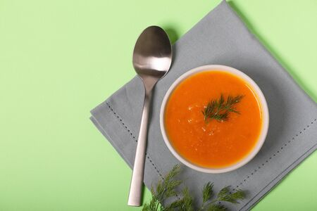 Pumpkin and carrot soup with fresh dill on light green pastel background
