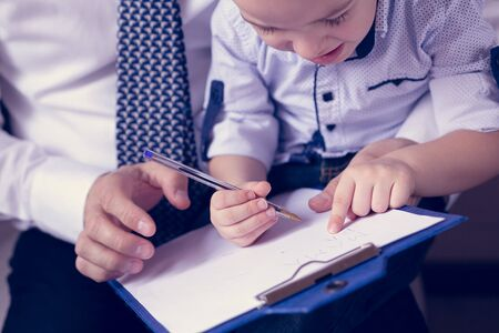 Work at home. Father teaches to his young son. Close up of adult hand are holding child hand to writing.