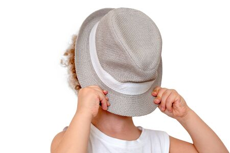 Holidays with children. Kid he covers his face with a straw hat isolated on white background. Summer time, vacation concept. Minimal. Soft focus.