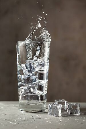 Glass with water and ice on gray surface