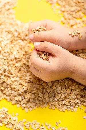 Healthy food. Raw oat flakes in children hands enclosed in the safe hands of the parent from above. Vertical orientation Archivio Fotografico