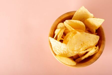 potato chips in a bowl on pink background Archivio Fotografico