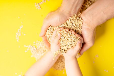 Healthy food. Raw oat flakes in children hands enclosed in the safe hands of the parent from above. Horizontal orientation