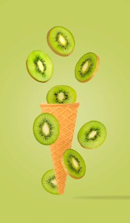 Flying isolated fruit into ice cream cone. Kiwi on pastel green background for packaging design and advertising. Clipping path included.