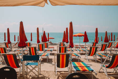 window on the sea and beach equipped with sun beds and umbrellas. Summer time. Vacation concept