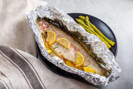 Fresh baked salmon trout in an aluminum foil Archivio Fotografico - 159198890