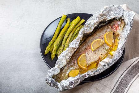 Fresh baked salmon trout in an aluminum foil Archivio Fotografico - 159234436