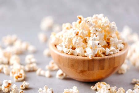 Homemade popcorn in a wooden bowl on a grey background Archivio Fotografico - 160651419