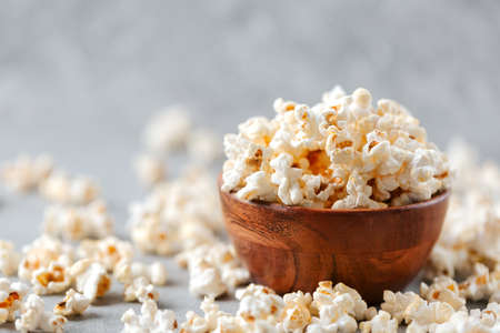 Homemade popcorn in a wooden bowl on a grey background Archivio Fotografico - 161048375