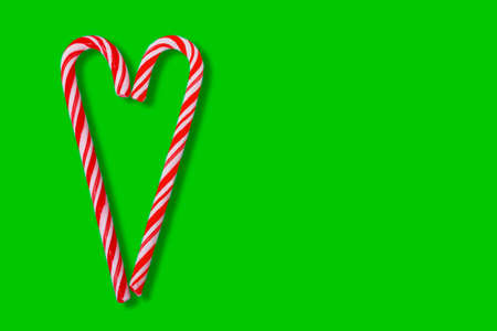Christmas design elemen with two red striped candy cane in heart isolated on green background Archivio Fotografico
