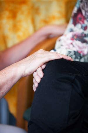Daughter confronting her elderly mother rest her hands on her knees