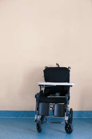 Wheelchair near wall in home for the elderly Archivio Fotografico
