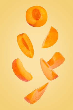 Falling down apricot slices isolated on trendy coloured background