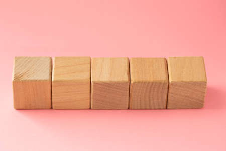 Abstract geometric real wooden cube with surreal layout on pink background Archivio Fotografico