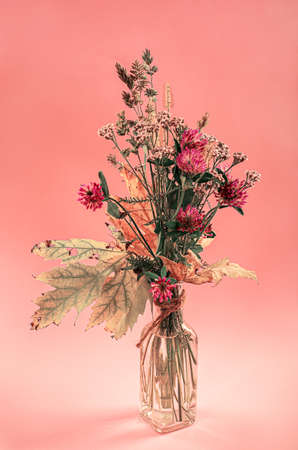 transparent vase with with autumn flowers on the pink background