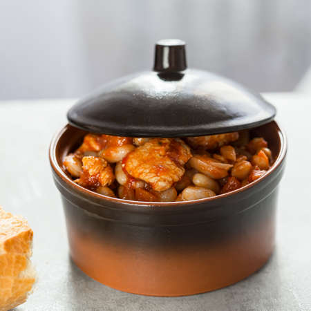 Pork stew with white beans in a brown bowl. Archivio Fotografico