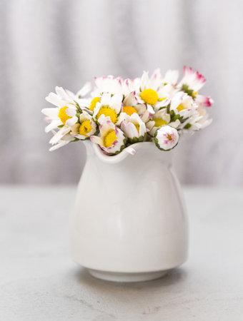 Beautiful daisy flowers in ceramic white vase on ultimate gray Archivio Fotografico
