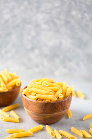 Bowl of raw penne pasta on ultimate gray background