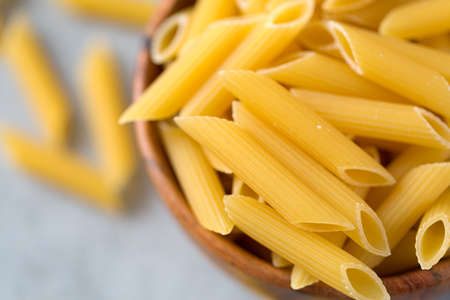 Flat lay of bowl with raw penne pasta on ultimate gray Archivio Fotografico