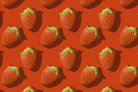 Whole strawberries fruit pattern on red color background