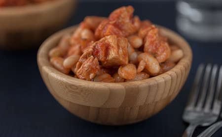 Pork stew with white beans in a wooden bowl. Archivio Fotografico