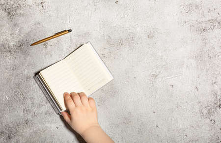 Notebook and pen on a gray concrete background. Female workspace. Top view, flat lay, copy space