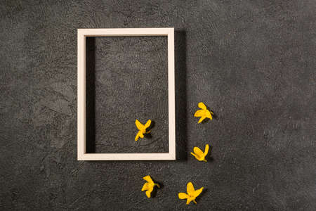 Creative flat lay flowers composition. Light yellow flowers, empty photo frame for text on black background. Wedding. Birthday. Valentines Day. Mother's day. Top view, copy space.