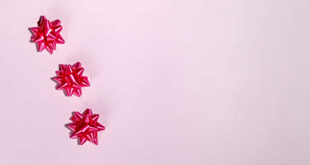 Red gift bow on pink background template for posters and banners
